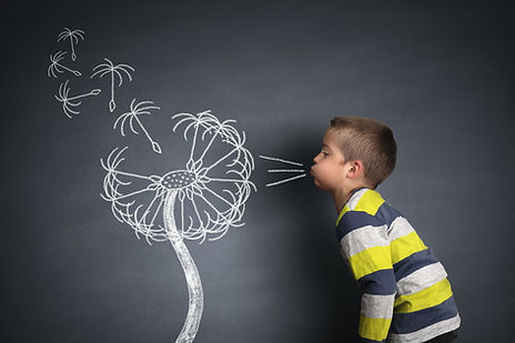 Child blowing dandelion seeds on a black