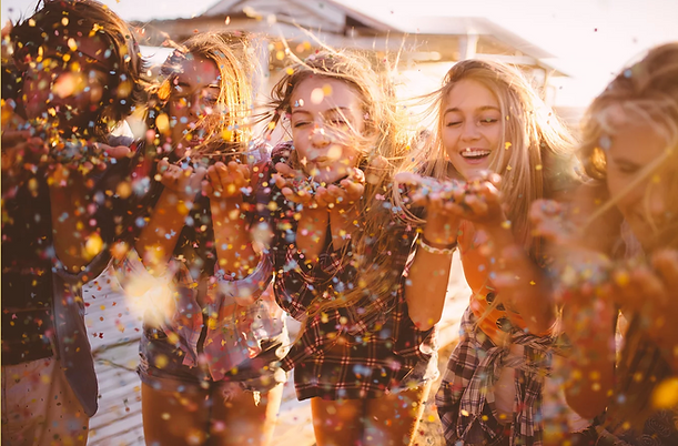 Girls blowing glitter and smiling