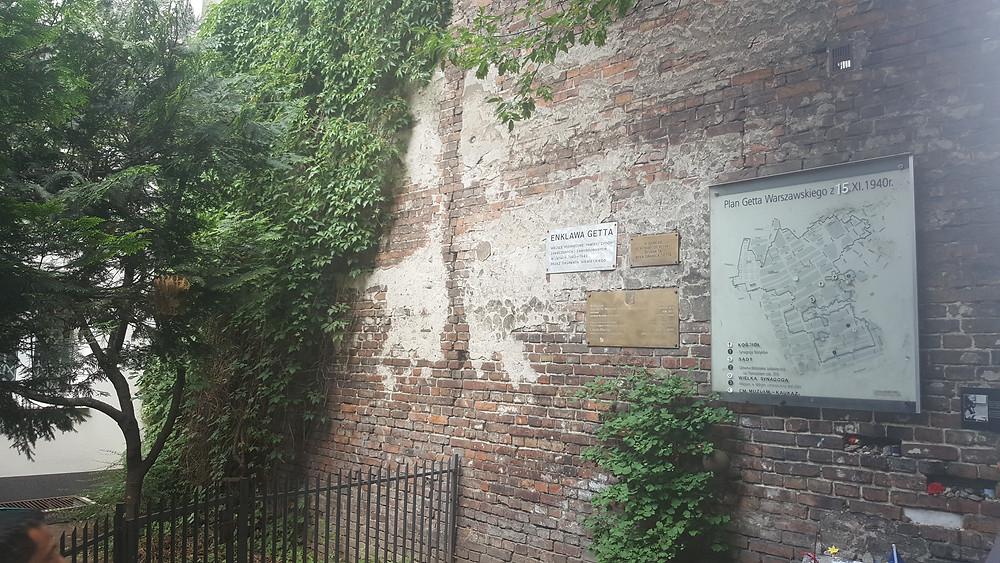 שרידי חומת גטו ורשה עם לוח שקבע עליו נשיא מדינת ישראל חיים הרצוג ב 1992