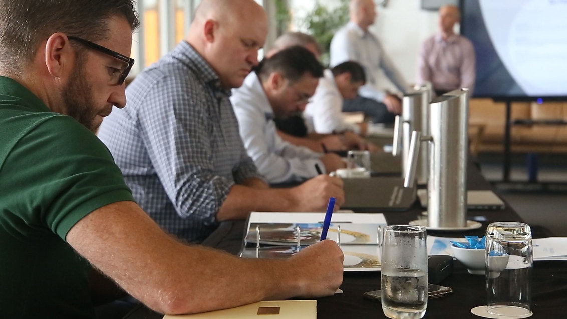 Photo of accountability program participants writing something down on paper