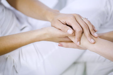 Nurse holding hand of someone in palliative care.