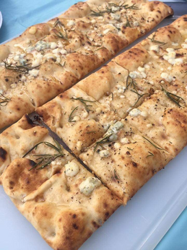 Homemade flatbread topped with rosemary, arctic thyme finishing salt, smoked honey, crumbled gorgonzola, and basil infused olive oil.