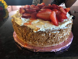 A homemade lemon cake, filled with lemon pudding and topped with homemade American lemon buttercream and fresh strawberries.