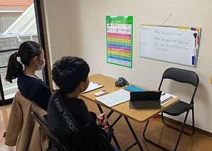 two jr. high students reading words on a whiteboard at SEC English School