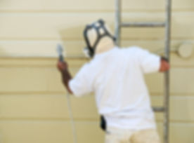 A man on a ladder uses spray gun to pain