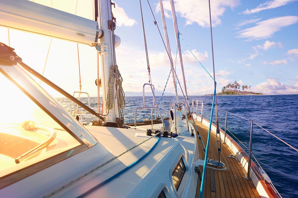 Sailboat motoring toward an island.