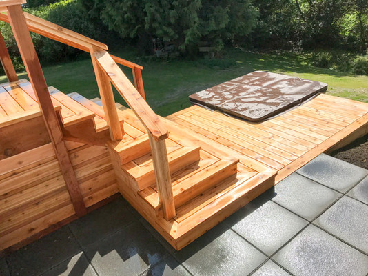 Cedar stairs with hot tub surround, 2x2 concrete pavers.