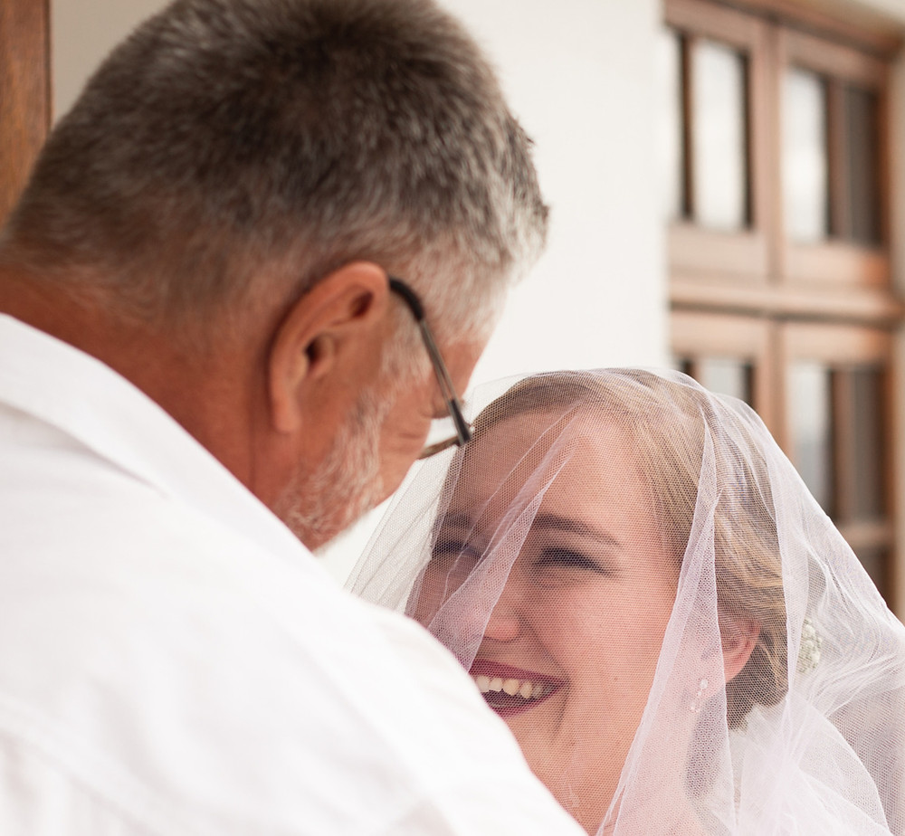 The Father smiling at his daughter. She has tears in her eyes as she smiles at her father through her veil. This is an intense and beautiful moment between the Father and daughter.