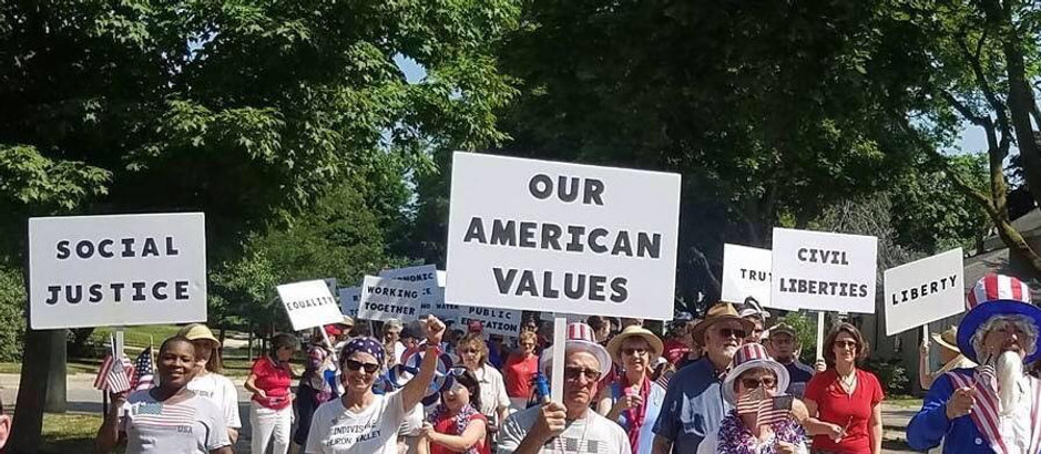 Indivisible Huron Valley Values on signs in July 4th Parade