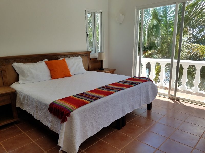 large bed in villa room with ocean view and palm trees