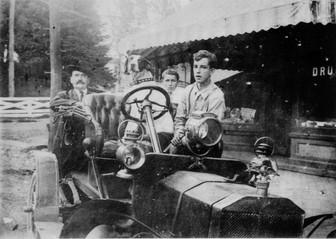 People in car in front of Ellett Drug