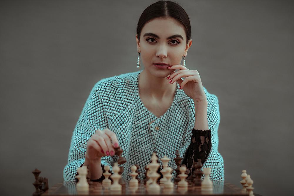 Mulher jovem posa jogando xadrez com seriedade e ar de estrategista