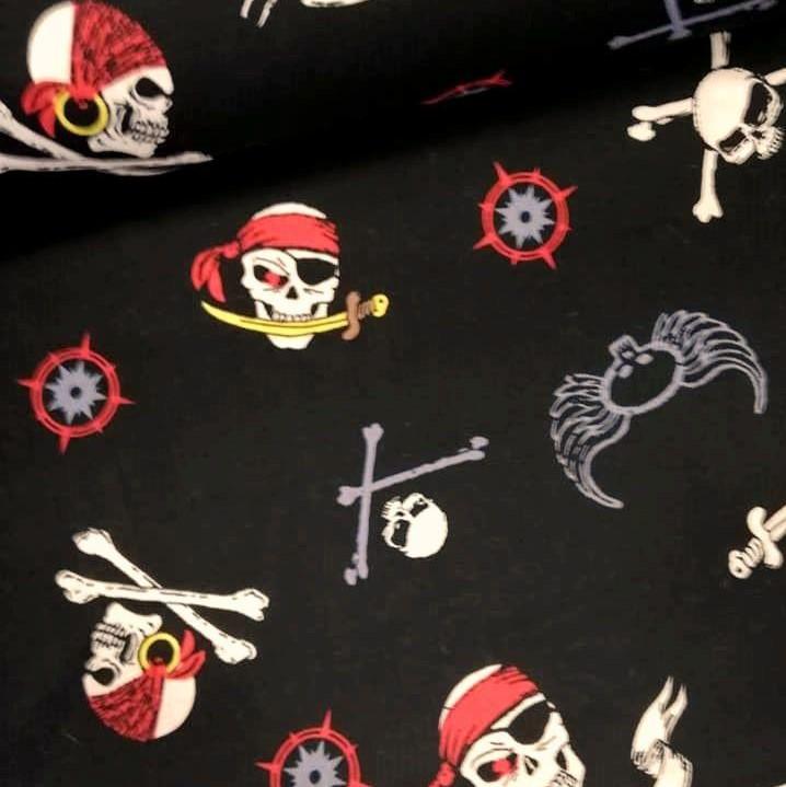 Tejido calaveras piratas sobre fondo negro