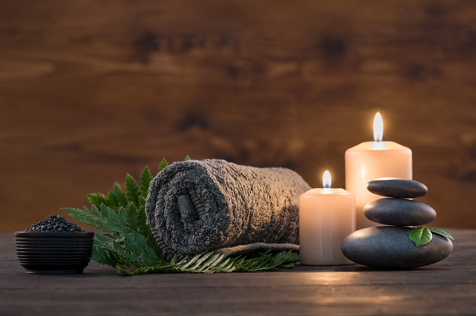 Towel on fern with candles and black hot stone on wooden background. Hot stone massage set
