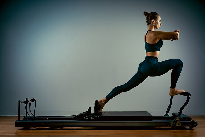 Young girl doing pilates exercises with a reformer bed. Beautiful slim fitness trainer on