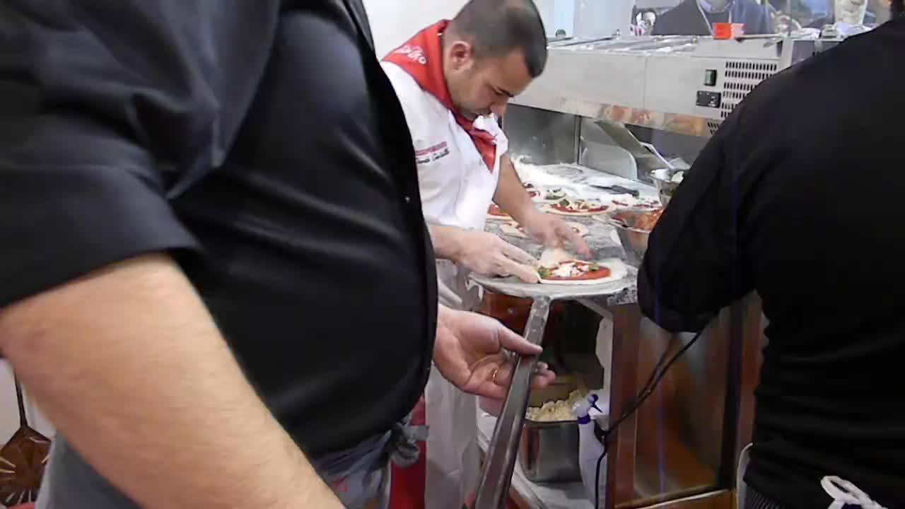 """Pizze """" a portafoglio """". Due maestri pizzaiuoli lavorano senza sosta alcuna con lo scugnizzonapoletano"""