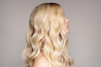 Blonde dame met prachtig glanzende haren, verzorgt met conditioner van O'right, Aloxxi en Medavita