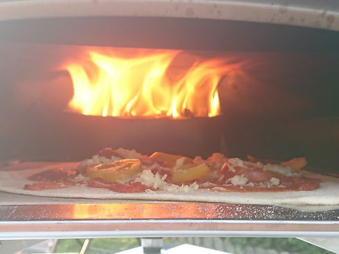 Pizza cooking under a flame