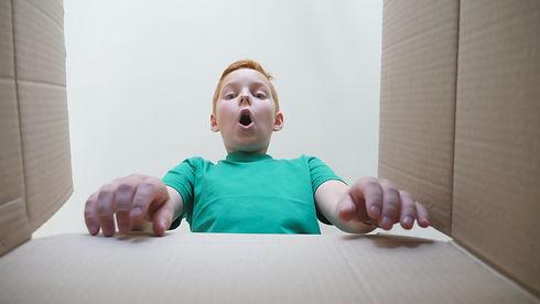 Little child opens carton box and pullin