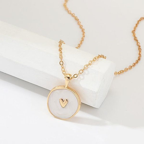 Gold necklace with white enamel inspired surrounding an embossed heart 18inch in length. with lobster clasp.