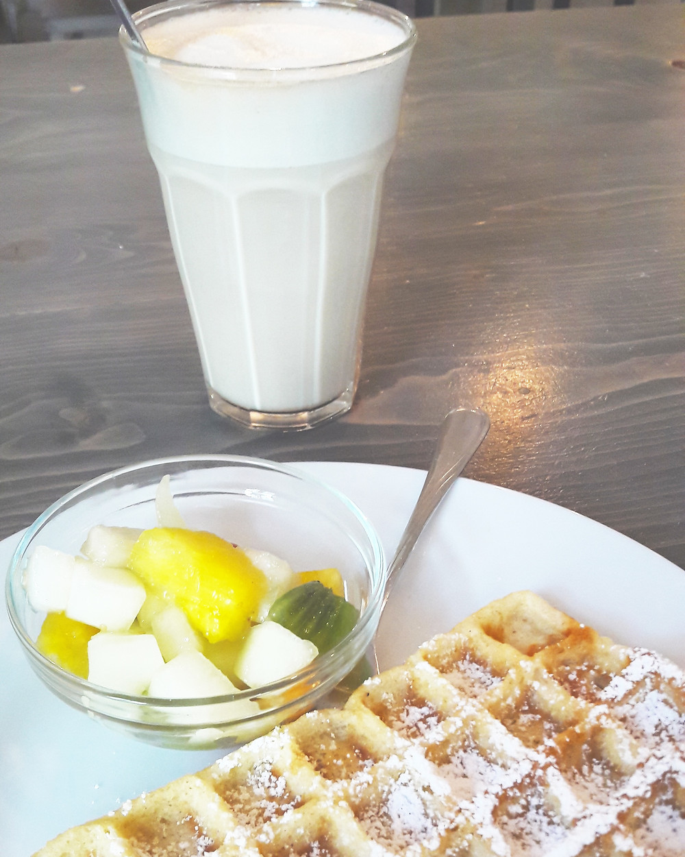 chai latte and waffles with fruit in white rabbit's room cafe munich
