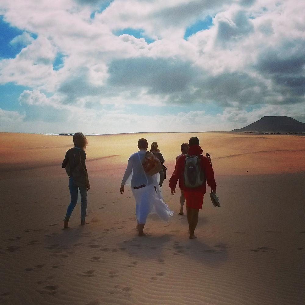 people walking across Corralejo sand dunes