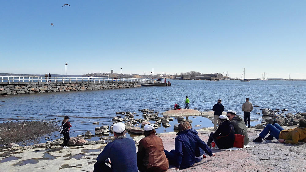 people in sailor hats sitting by the water in Helsinki
