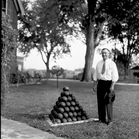 Carbondale businessman Clyde Smith poses next to a stack of cannon projectiles at the Mound City National Cemetery, circa 1939.
