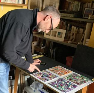 Richard Nicholls examining artwork by Cherrie Mansfield
