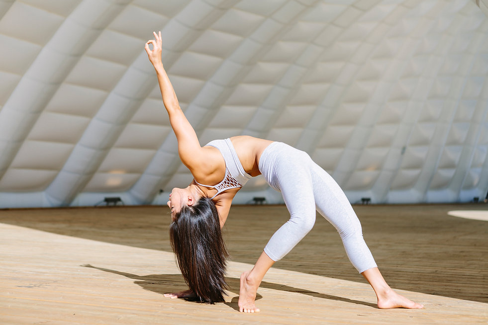 Melissa Tung Corporate Yoga and Wellness - Melissa in wildthing pose one hand in mudra.