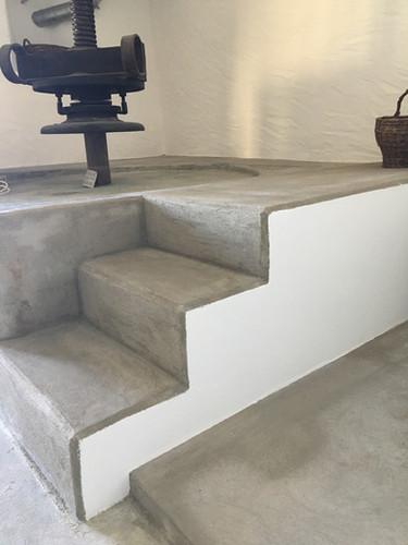 Construction d'un escalier donnant accès à la plateforme du pressoir par piquage du béton au fond de la pièce
