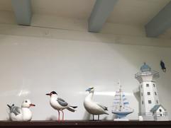 les oiseaux en bois (Bretagne) et un phare miniature donnent une ambiance maritime, en accord avec les poutres dans un ton ciel
