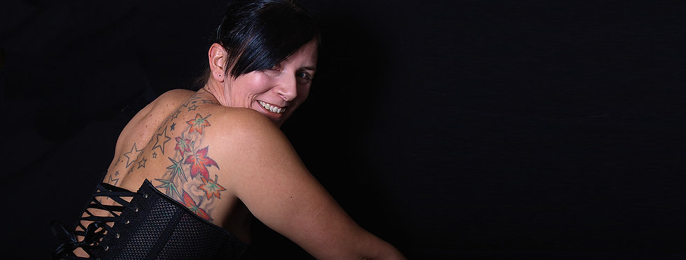 A mature woman wearing a corset smiles in to the camera as she shows off her back tattoos.