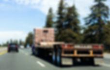Semi truck on highway with empty flatbed