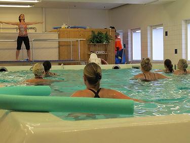 En bassäng med kvinnor som gör vattengymnastik.
