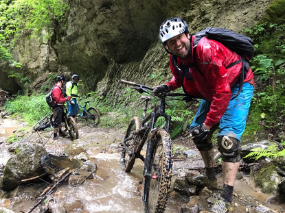 Happy customer washing off his muddy bike in the stream