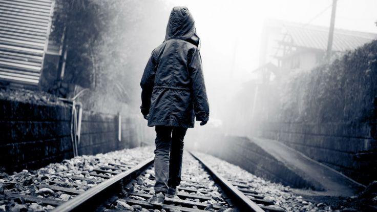uncertainty: boy walking alone on train tracks