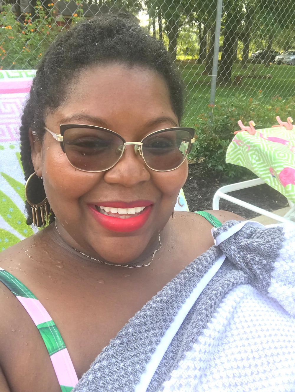 Courtney Tierra smiling while wearing sunglasses and bright lipstick while wrapped in a beach towel.