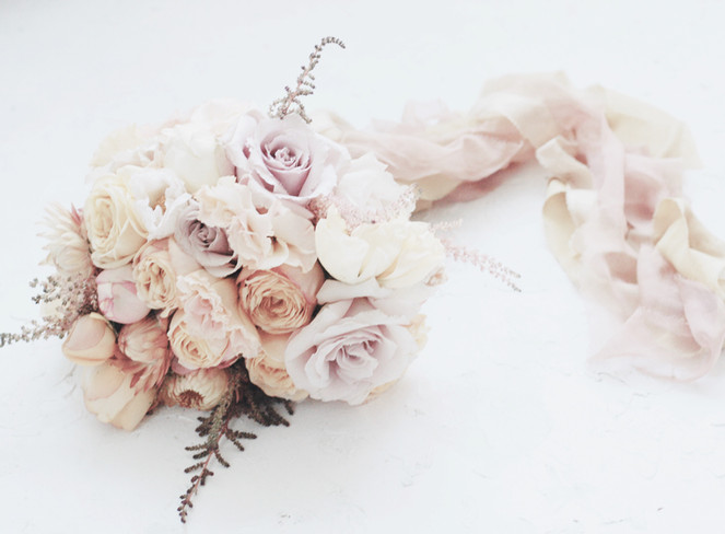 bridal bouquet in tones of apricot and mauve tied with silk ribbon