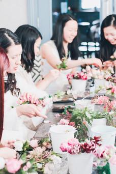 ladies sitting around table making flower crowns
