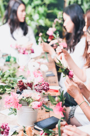 table with vases of flowers and hands creating flower crowns