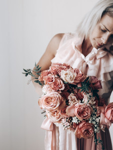 florist holding bouquet of apricot and peach wedding flowers