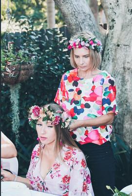 lady fixing flower crown to ladies head