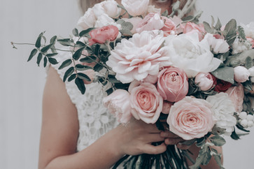 flower girl holding posy of flowers in pinks