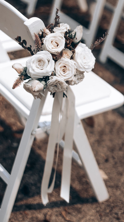 white posies of flowers tied to chairs
