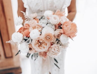 bride holding pretty bouquet of peonies and rannunculas in shades of apricot, peach and white