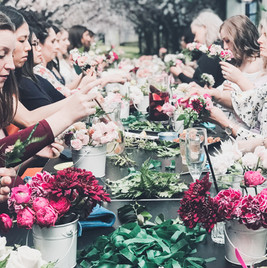 table with vases of pink flowers and ladies making flower crowns