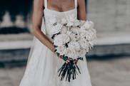 bride holding bunch of long stemmed white roses