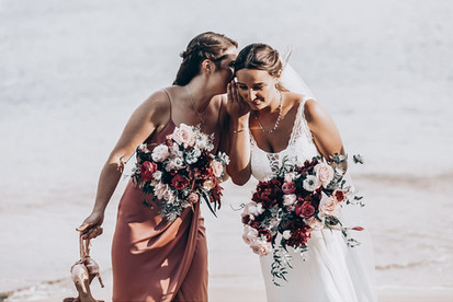 bride and bridesmaid on beach holding beautiful bouquets