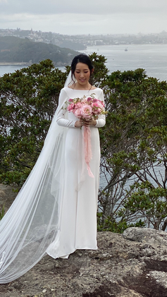 bride holding bouquet of pink and apricot flowers